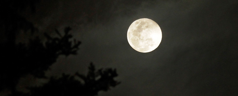 photo of a full moon against a cloudy sky